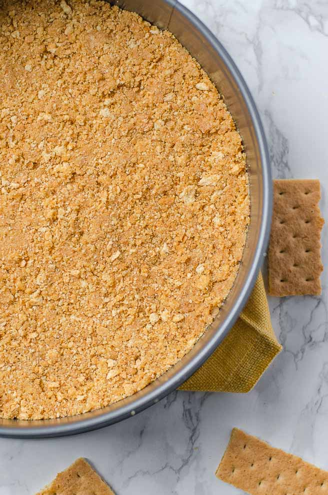 close up of the graham cracker crust in a springform pan