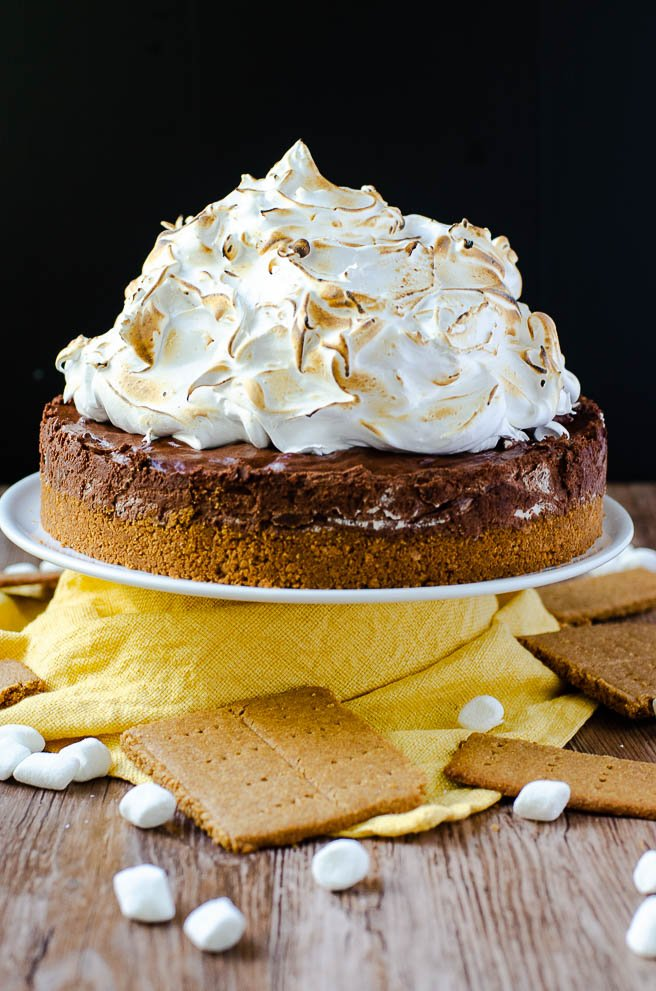 Sky high s'mores pie recipe on a white cake stand. It is surrounded by a yellow napkin, marshmallows, and graham crackers