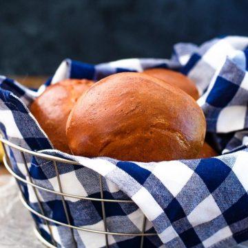 Basket of hamburger buns on a blue gingham kitchen towel.