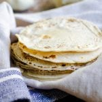 A stack of homemade tortillas in a kitchen towel