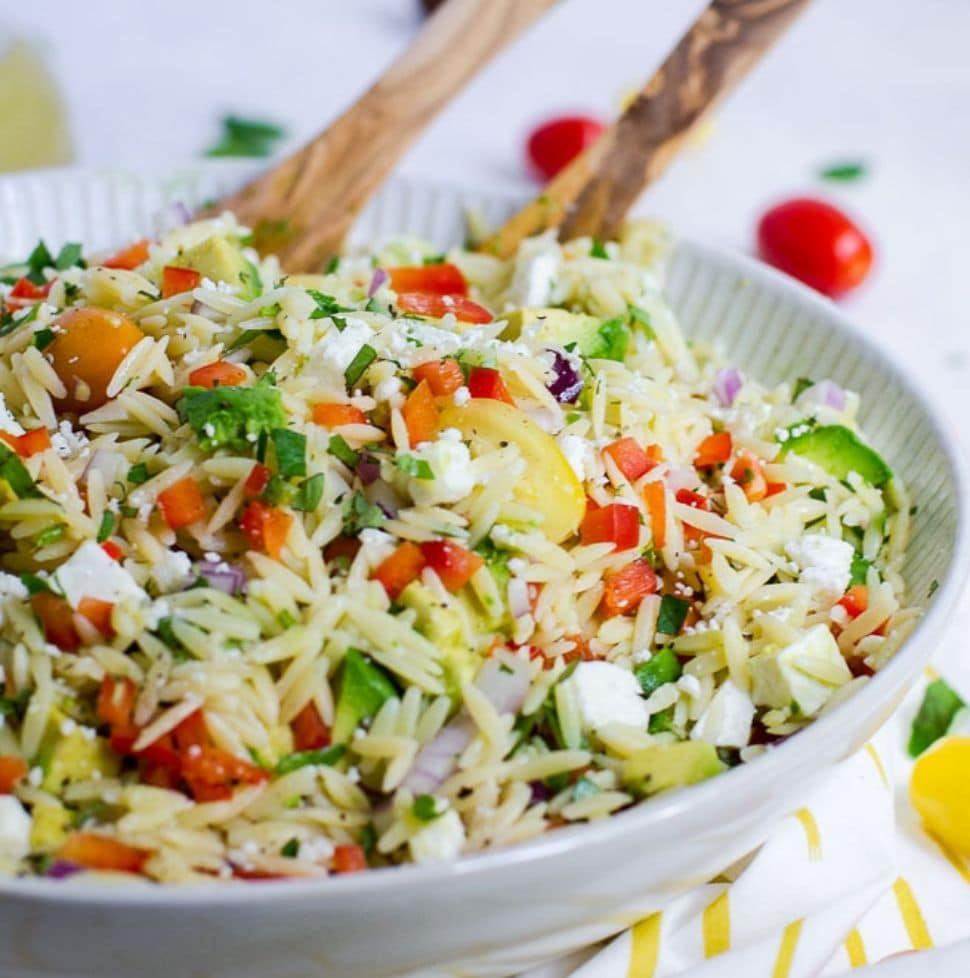 Bowl of pasta salad with wooden serving spoons
