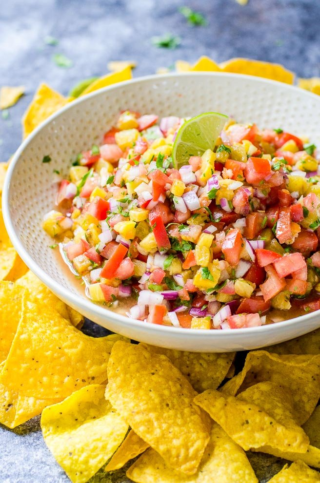 a white bowl of grilled pineapple salsa surrounded by chips