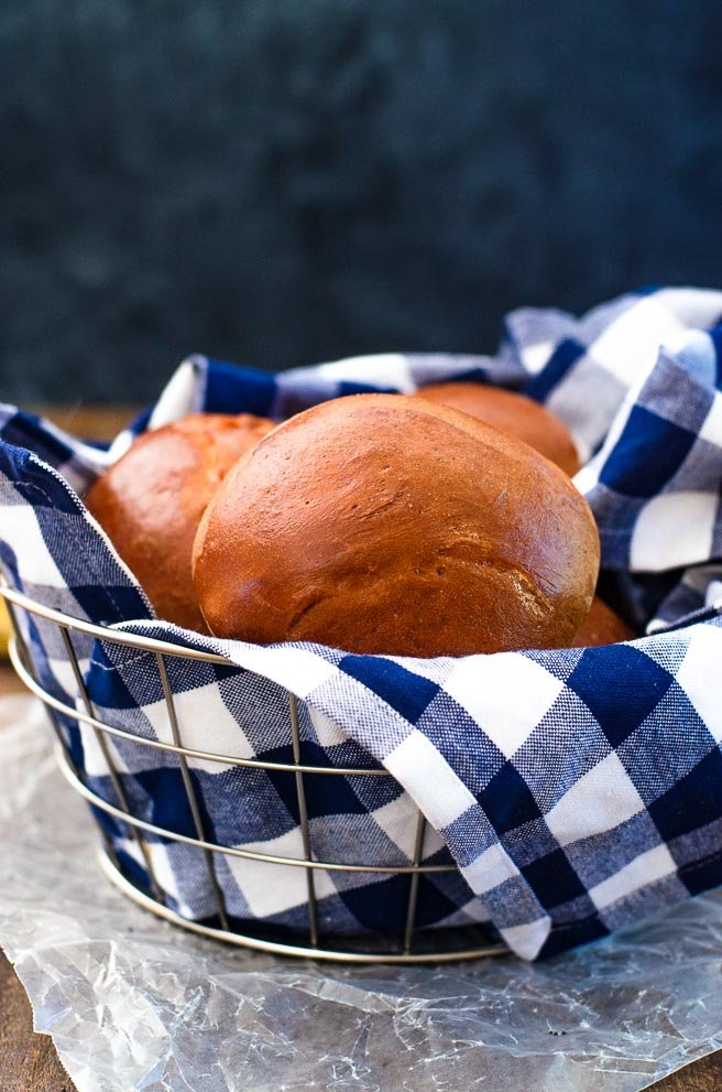 basket of buns wrapped in a blue gingham kitchen towel