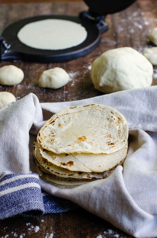 corn tortillas being kept warm in front of dough and a cast iron tortilla press