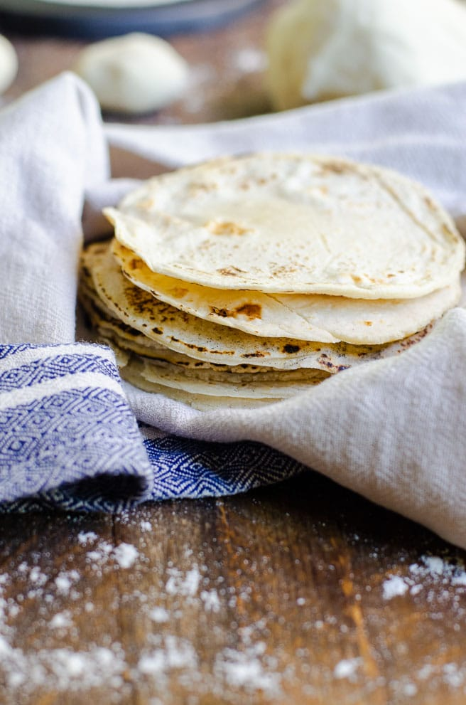 a stack of homemade corn tortillas in a tan and blue kitchen towel