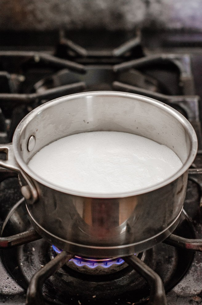 a pot of milk on a gas burner