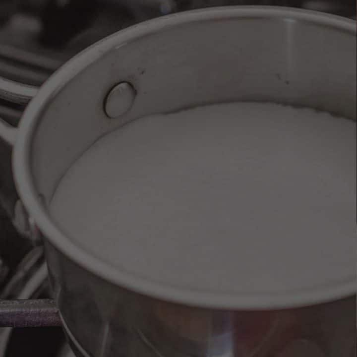 pot of scalded milk on a cooktop with a black overlay.