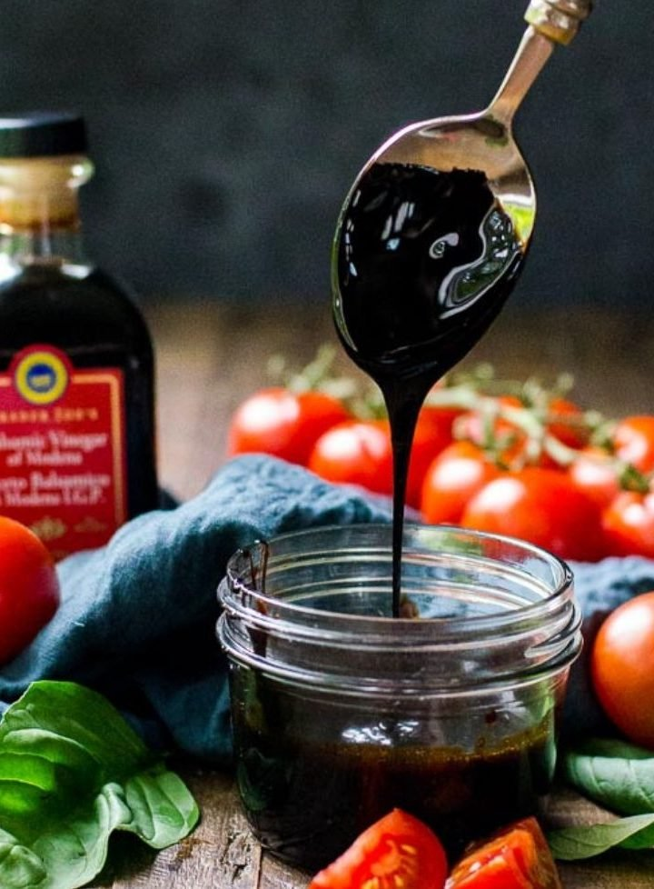 A jar of balsamic reduction with a spoon showing how thick it should be.