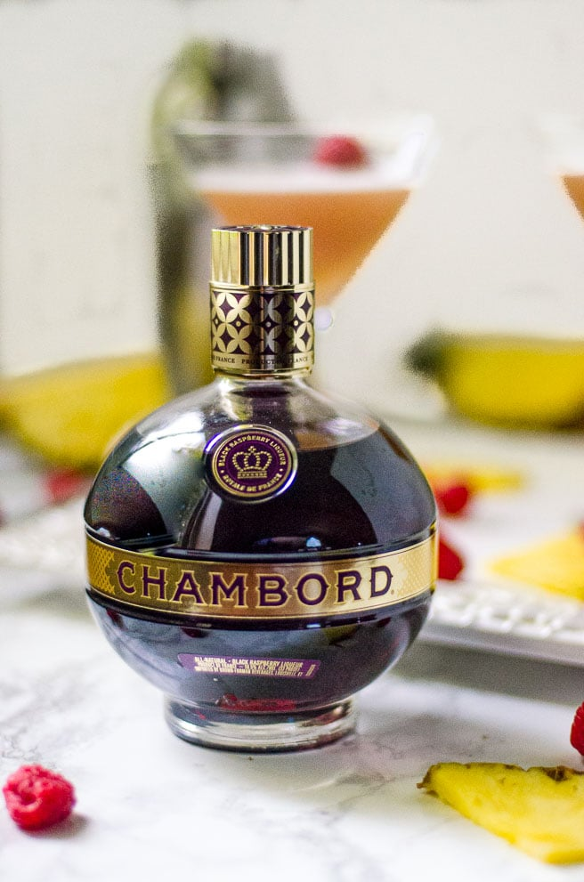 Bottle of Chambord surrounded by fruit garnishes for a cocktail.