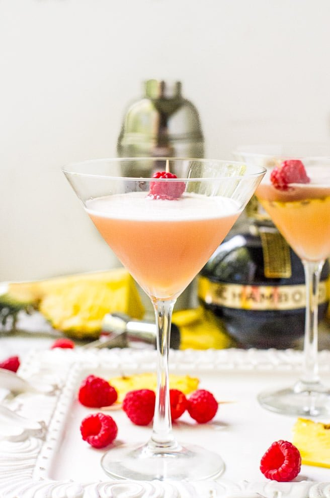 Two glasses of french martinis surrounded by fruit.
