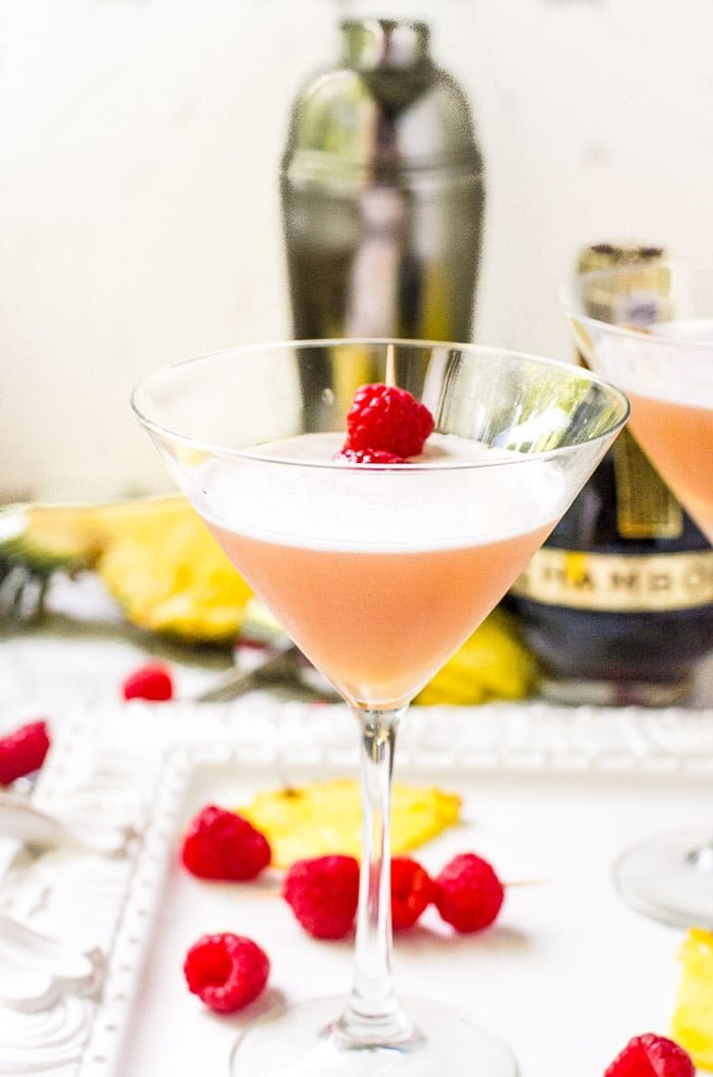 A garnished french martini recipe on a white tray.