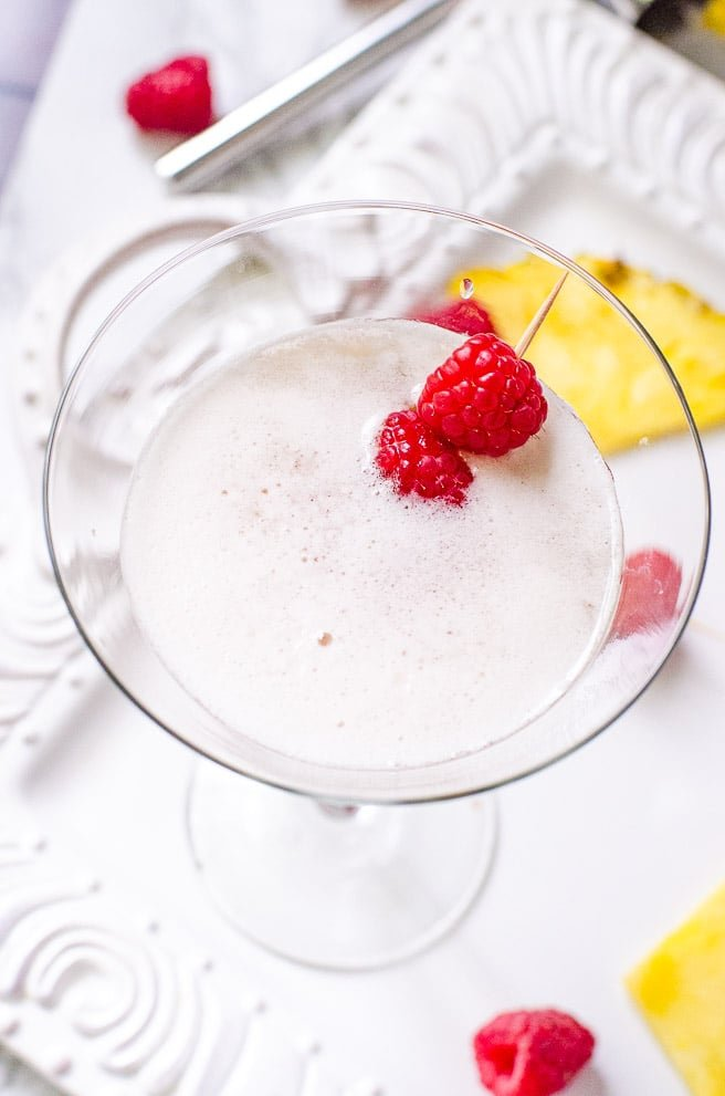 Overhead view of the inside of a cocktail glass garnished with raspberries. It shows the foam from shaking instead of stirring the drink.