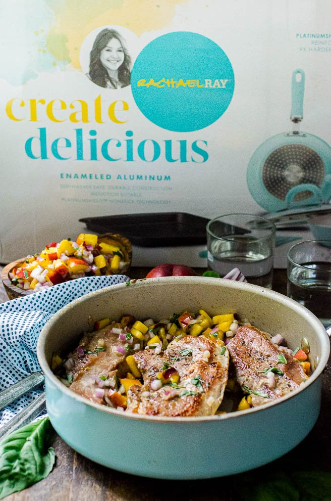 a blue Rachel Ray skillet in front of the watercolor Create Delicious cookware box.