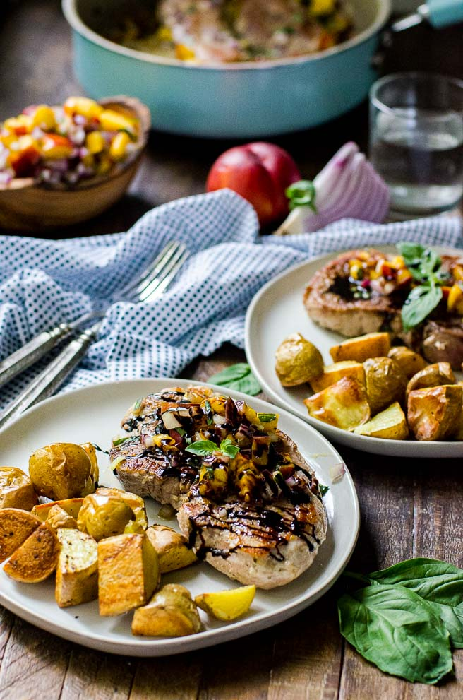 A table set with two plates of pan seared pork chops and roasted potatoes