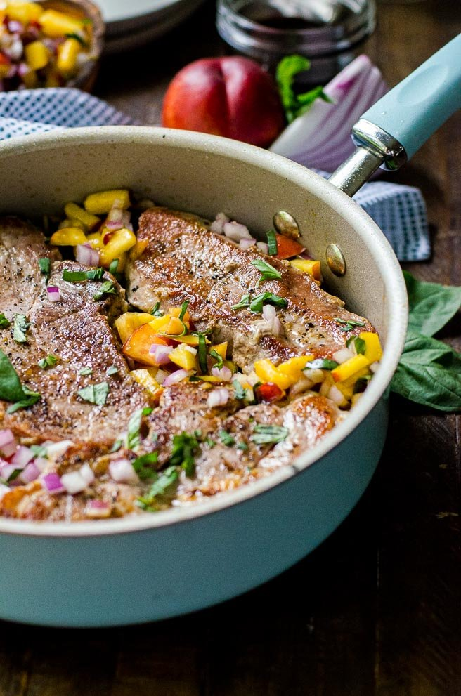 A blue skillet filled with pan seared pork chops and with nectarines