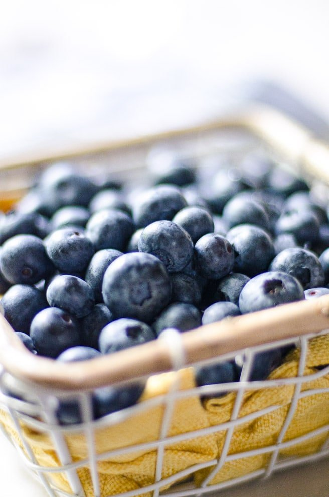 Close up of fresh blueberries in a small basket.
