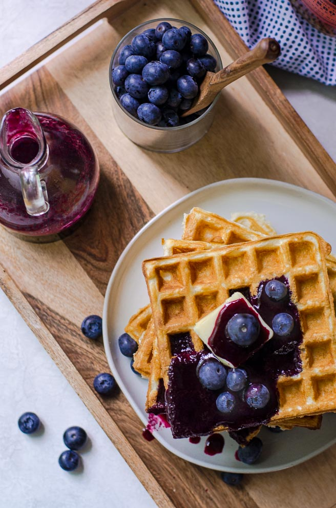 overhead view of a breakfast tray of waffles, blueberries, and syrup.