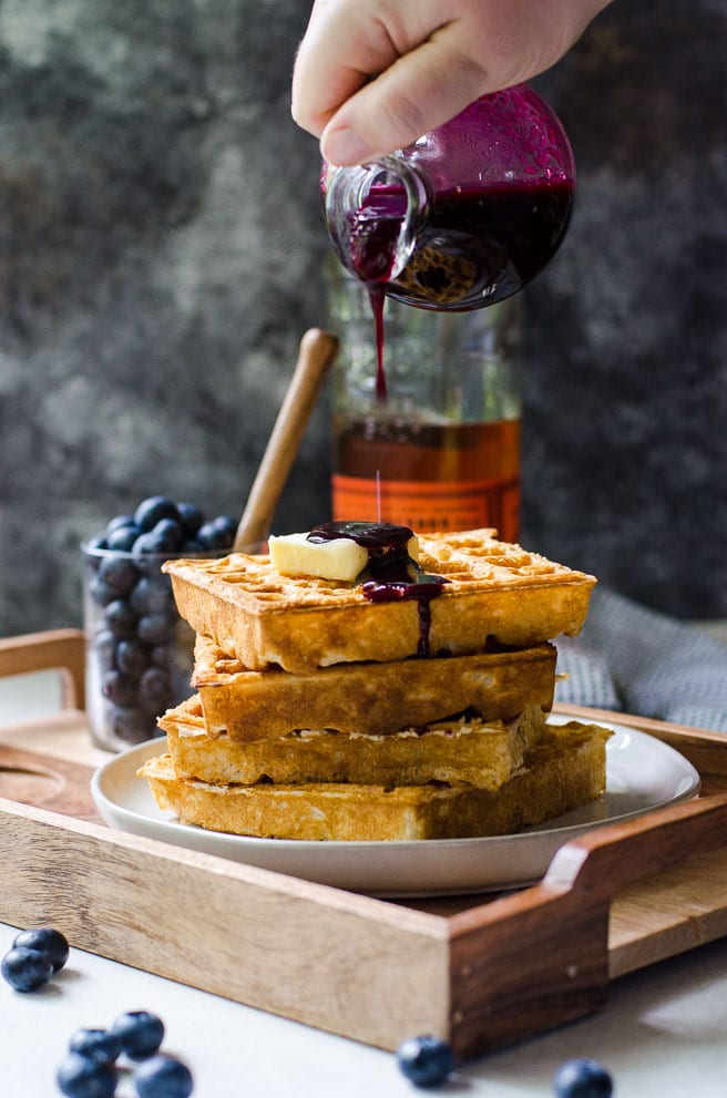 A hand pouring a bottle of blueberry syrup on waffles.