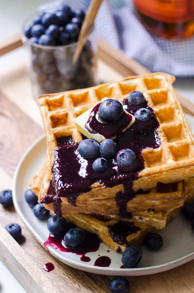 Blueberry syrup dripping off a stack of waffles.