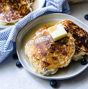 A large pat of butter and syrup on top of fresh blueberry pancakes on a gray plate.