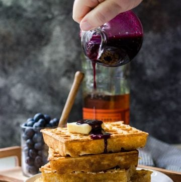 A container pouring blueberry syrup onto a stack of waffles.