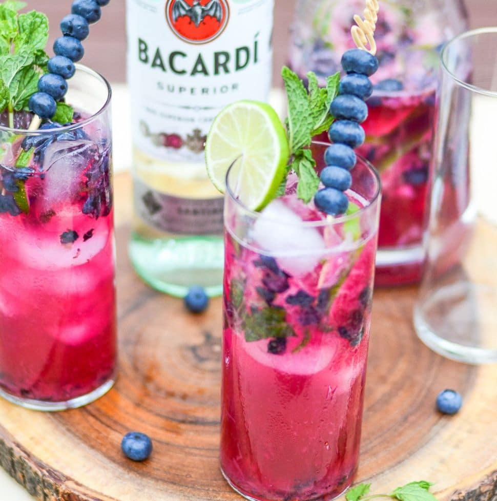 Two glasses of blueberry mojito in front of a bottle of bacardi rum.