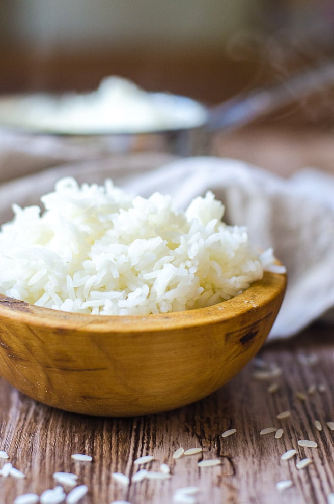 a wooden bowl overflowing with cooked white rice.