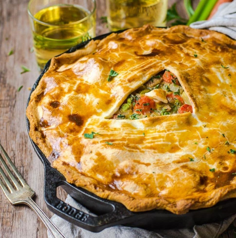 A fork next to a skillet pot pie made out of leftover turkey.
