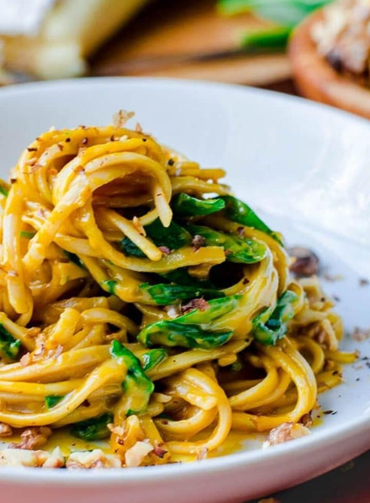 Creamy pumpkin pasta and spinach piled and swirled up high on a white plate.