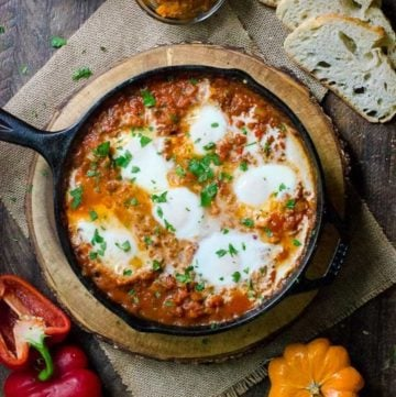 A cast iron skillet of pumpkin shakshuka surrounded by the ingredients used to make it.
