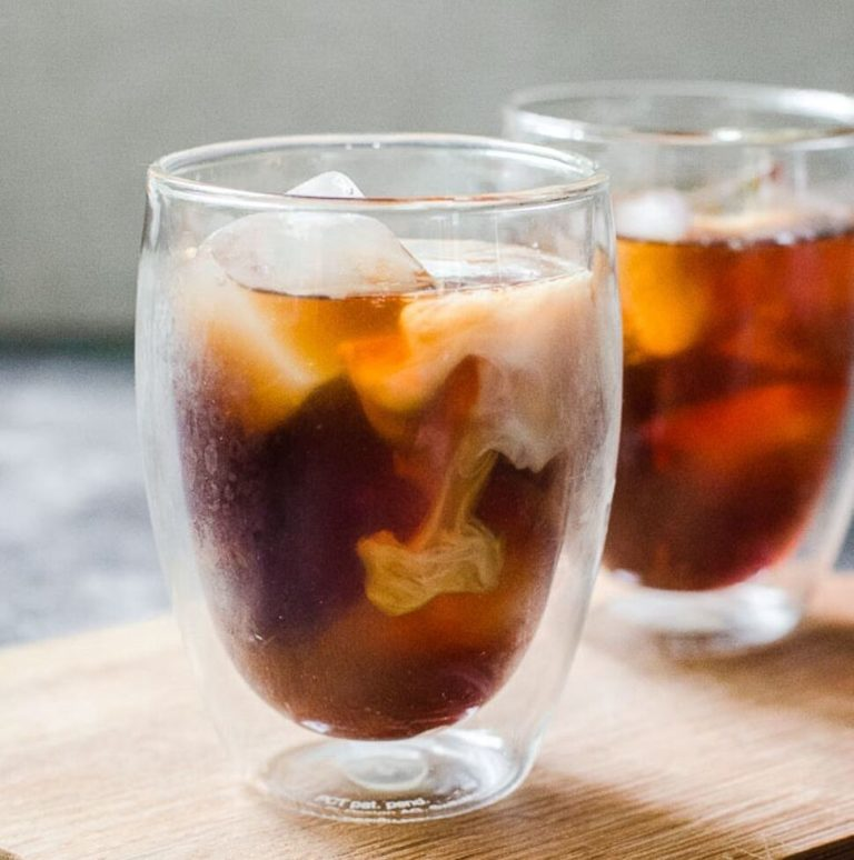 Cream swirling in a clear cup of iced cold brew coffee.