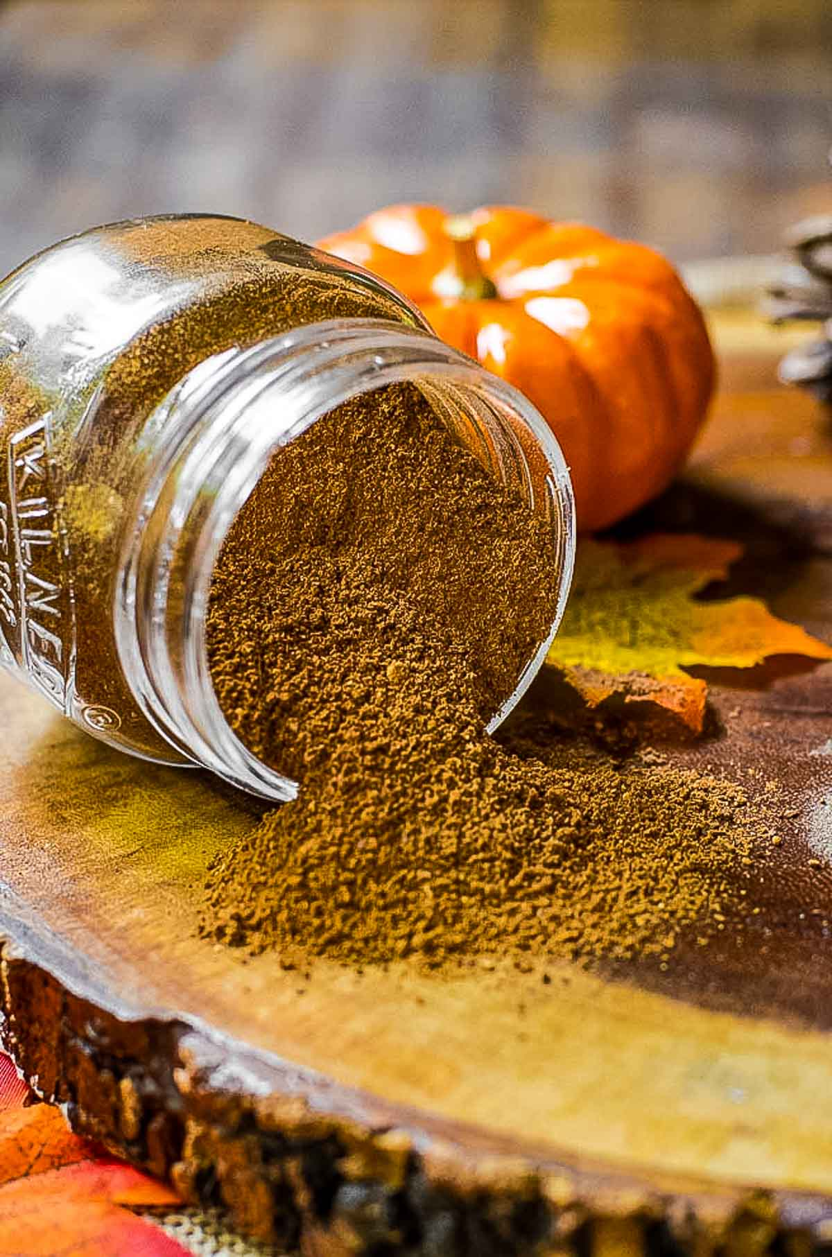 Homemade pumpkin pie spice spilling out of a jar onto a piece of wood.