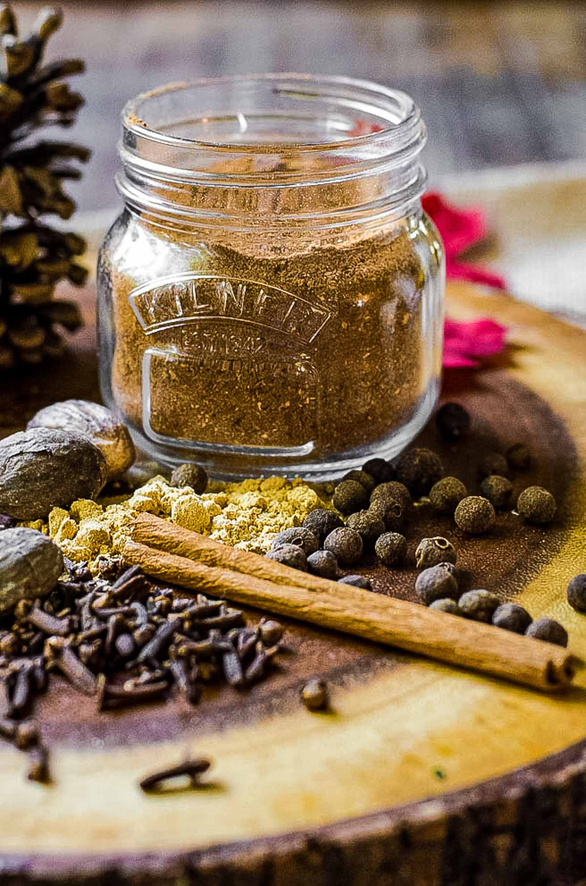 A jar of homemade pumpkin pie spice surrounded by whole spices.