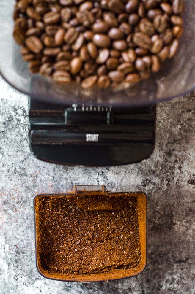 A grinder of coffee beans next to a container of coarsely ground coffee.