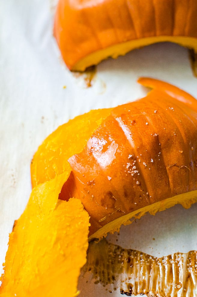 The pumpkin skin being peeled off of the roasted flesh.