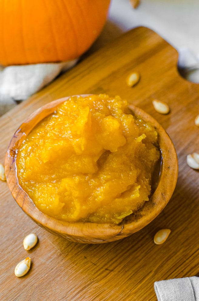 a wooden bowl filled with homemade pumpkin puree.