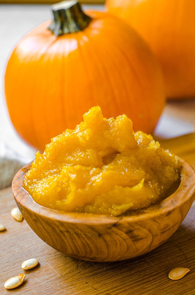 Close up of a wooden bowl filled with homemade pumpkin puree.