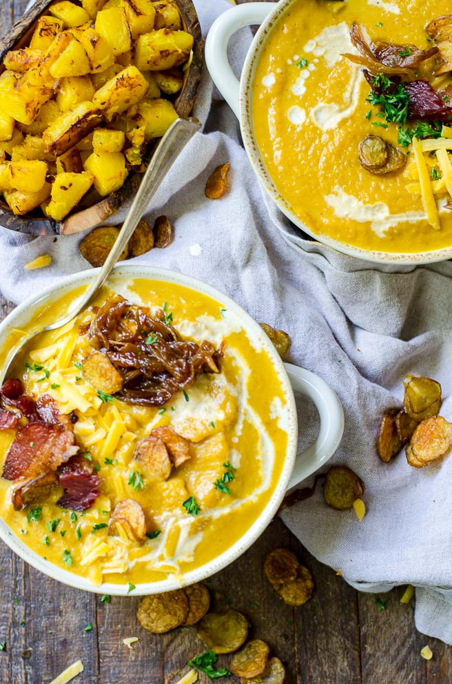 Two bowls of loaded pumpkin soup surrounded by numerous toppings.