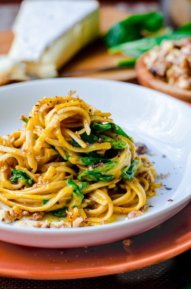 Linguine noodles and spinach piled up on a white plate.