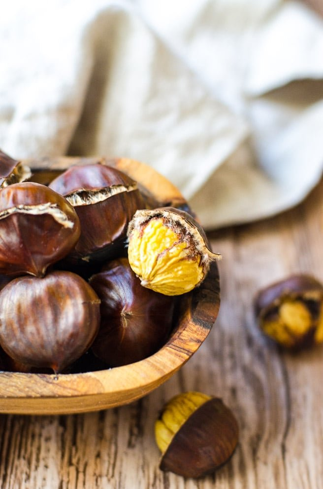 A peeled chestnut in a wooden bowl of roasted chestnuts