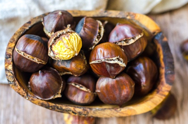 Overhead view of a wooden bowl filled with roasted chestnuts.  One is peeled to reveal the nut inside.