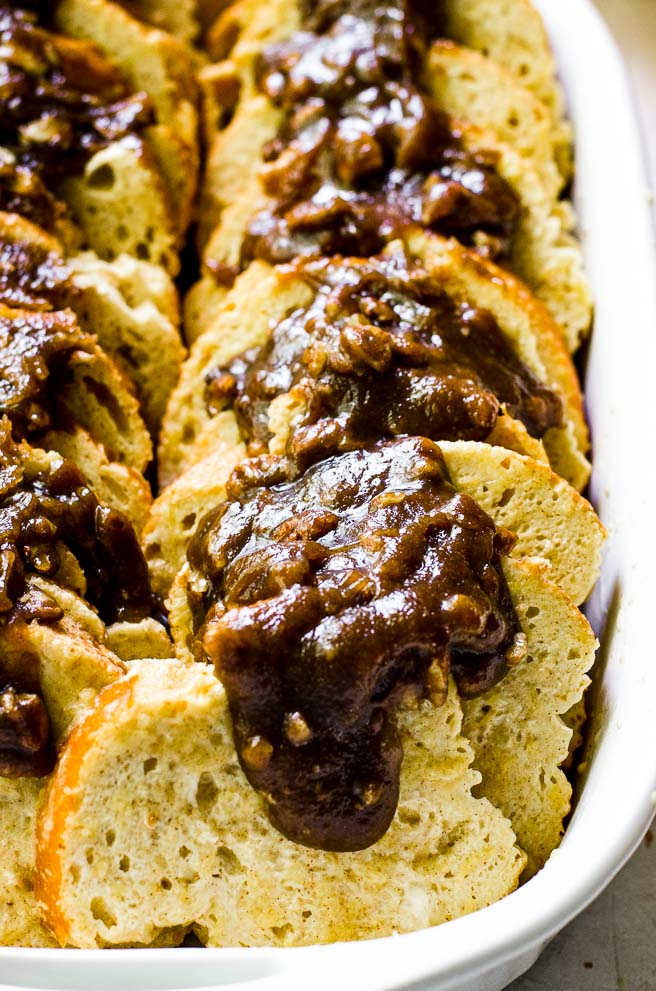 Close up of pecan praline brown sugar topping oozing over the top of bread slices.