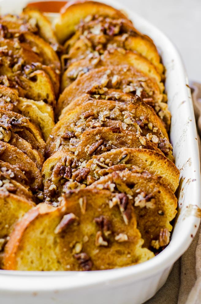 Two rows of cooked pumpkin french toast with pecan praline topping in a white baking dish.