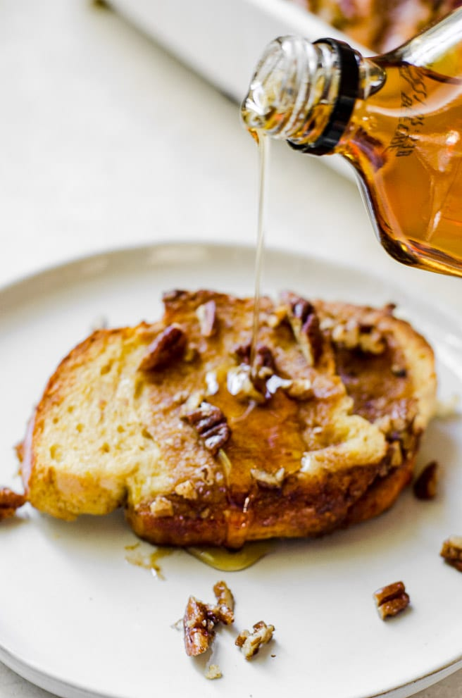 Syrup being poured out of a bottle and onto french toast.