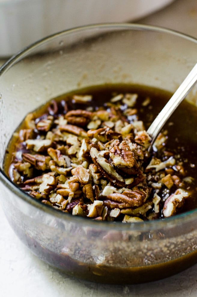 A spoon stirring chopped pecans into brown sugar for pecan praline topping.