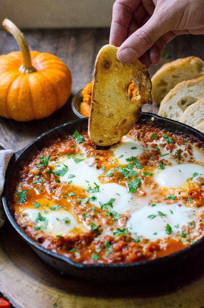 A hand dipping crusty bread into a pan of shakshuka.