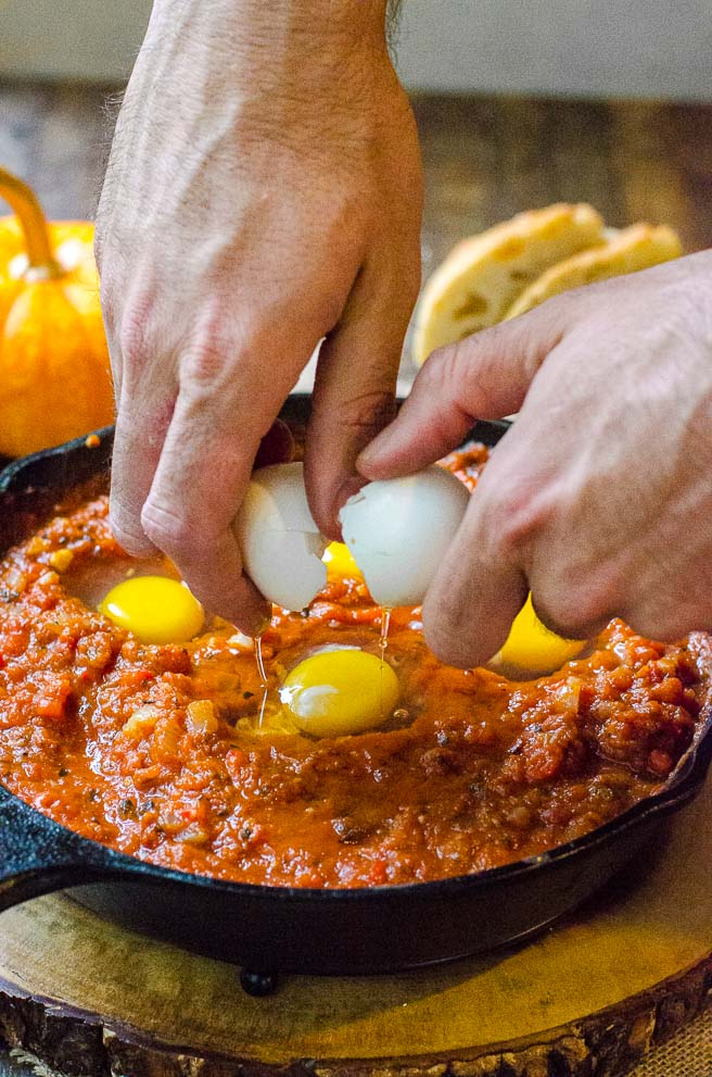 Hands cracking an egg into a pan of tomatoes.