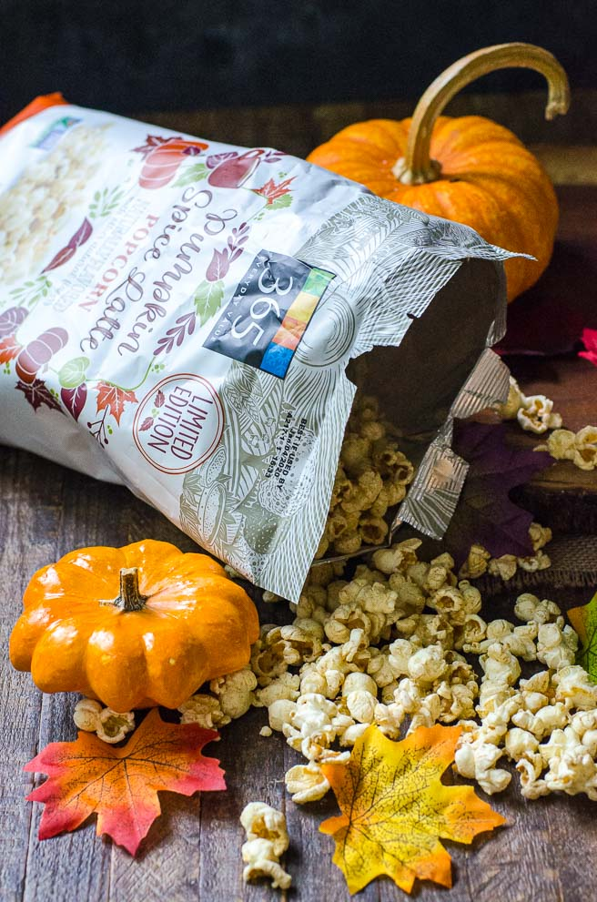 A bag of fall flavor pumpkin spice latte popcorn pouring out the popped kernels.