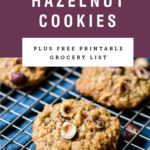 Chewy hazelnut oatmeal cookies on a cooling rack. Recipe title is above it on a purple background.