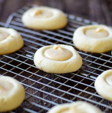 A cooling rack of brown butter iced thumbprint cookies.